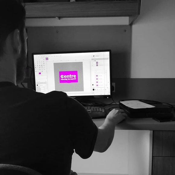 Person sitting at desk with a computer screen in front of them. The screen has the word Centre in a pink box, the rest of the image is black and white.