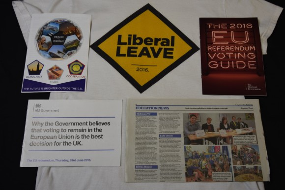 """A t-shirt with the words """"Liberal Leave on. This is surrounded by a booklet with the words """"The 2016 EU referendum voting guide"""" on, a newspaper, a leaflet with a globe on in the shape of a football with each side as a photograph and a booklet with the words """"Why the government believes that voting to remain in the European Union is the best decision for the UK""""."""