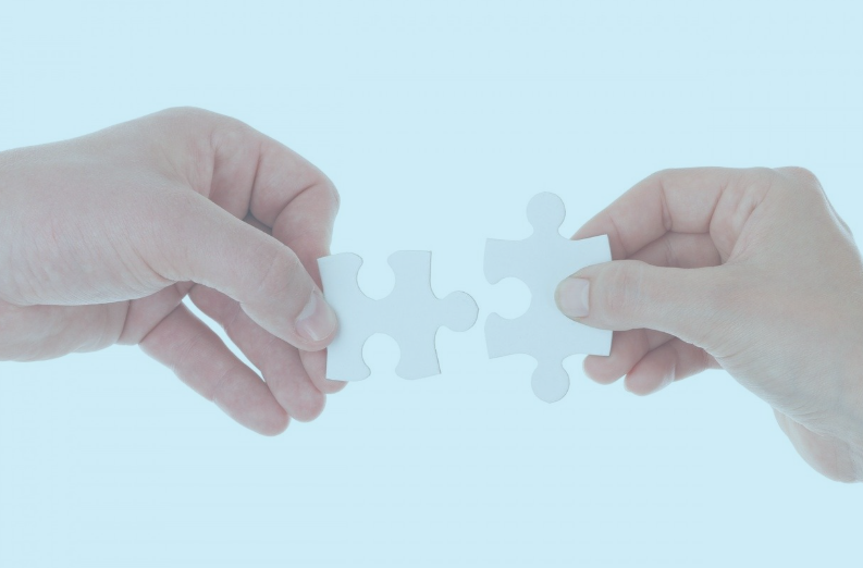 A blue image of two hands each holding jigsaw pieces.